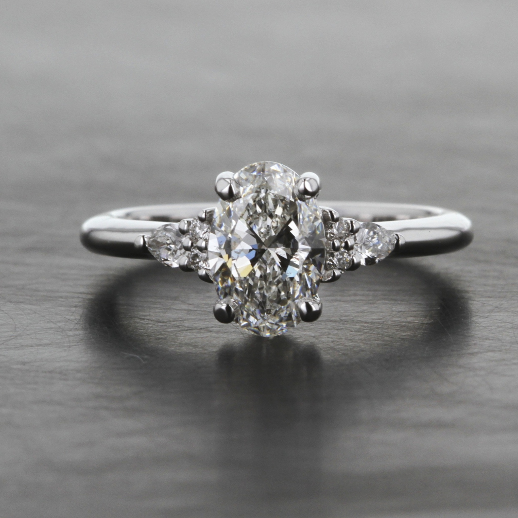 white-gold-oval-diamond-engagement-ring-custom-pear-side-stones-dainty-band.jpg