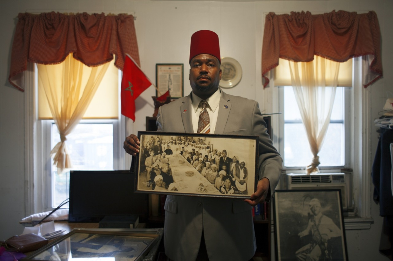 Kameelah Janan Rasheed. Sheik Azeem Hopkins-Bey of Temple #11 in Philadelphia, PA sharing some of the archival photographs and ephemera housed at the temple, 2016.