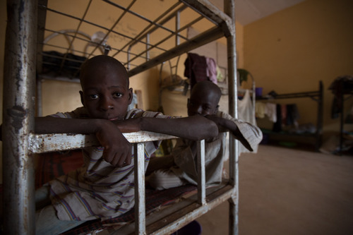 """Ten year old Stevenson and Jibrin in the mens living quarters in Damare IDP camp, Adamawa state. They are both from Michika, a town in northern Adamawa that is an area of heavy fighting between the Nigerian military and Boko Haram. """"My father and mother are not in the camp,"""" said Jibrin. Though numbers haven't been formally tracked as registration of displaced persons is still ongoing, Nigerian Red Cross volunteers who work in the camp say that there are many orphans whose parents whereabouts are unknown or feared dead. Their immediate family members are yet to be found or contacted. 2014, © Rahima Gambo"""