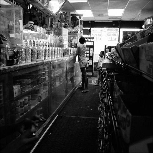 A girl and her brother buy food at the corner store, whose shelves are stocked with a wide variety of chips, candy, and soda. Like many similar establishments, there is no unprocessed or natural food available. Chicago, 2011.