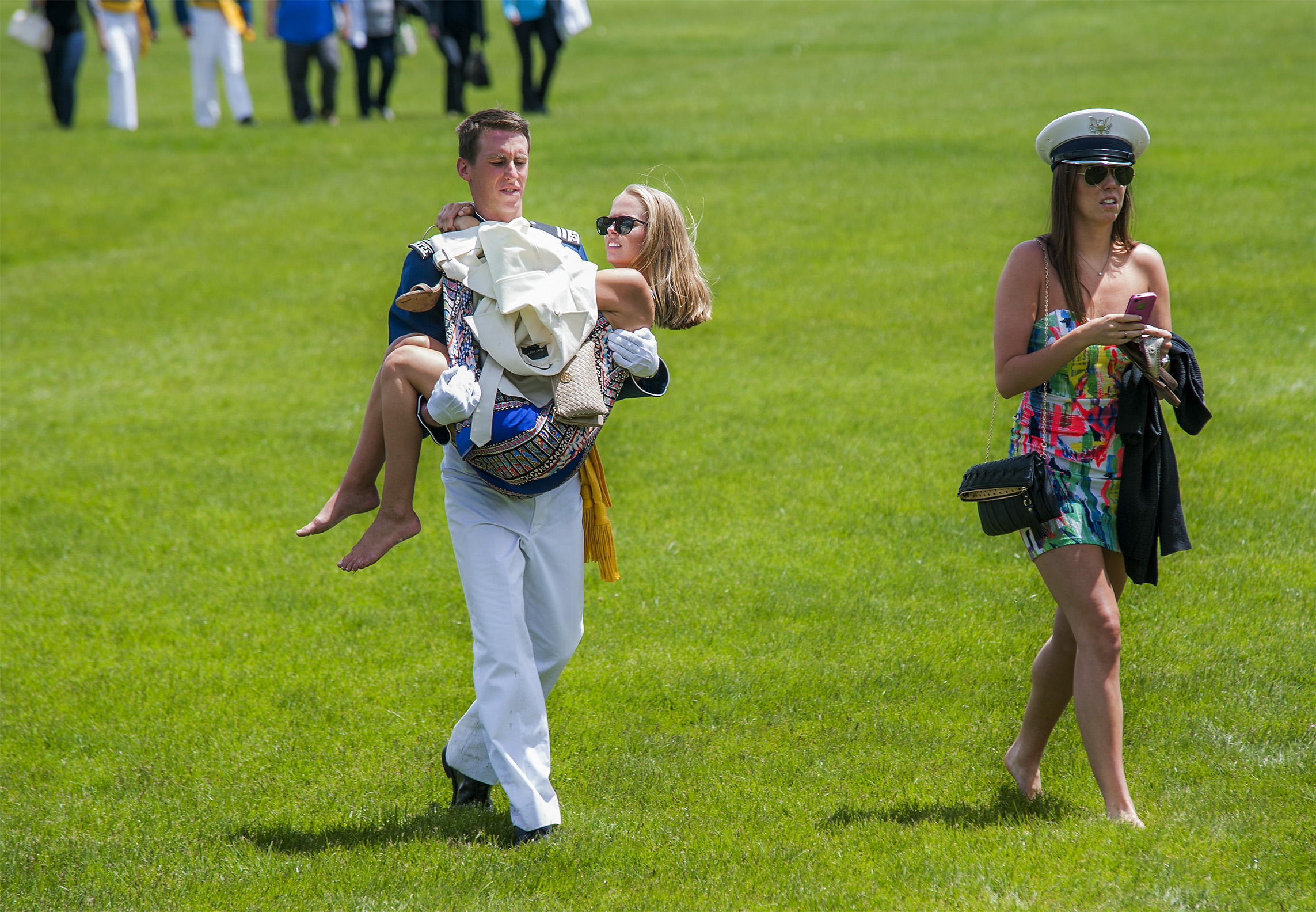 Cadet Landon Kinsey carries his girlfriend Hailey Jacob while walking with his sister Jenna Kinsey through the muddy field where the annual Air Force graduation parade was held to honor the Class of 2015 on Wednesday, May 27, 2015, in Colorado Springs, Colo. The Class of 2015 graduation will be held on May 28 inside Falcon Stadium at the Air Force Academy.