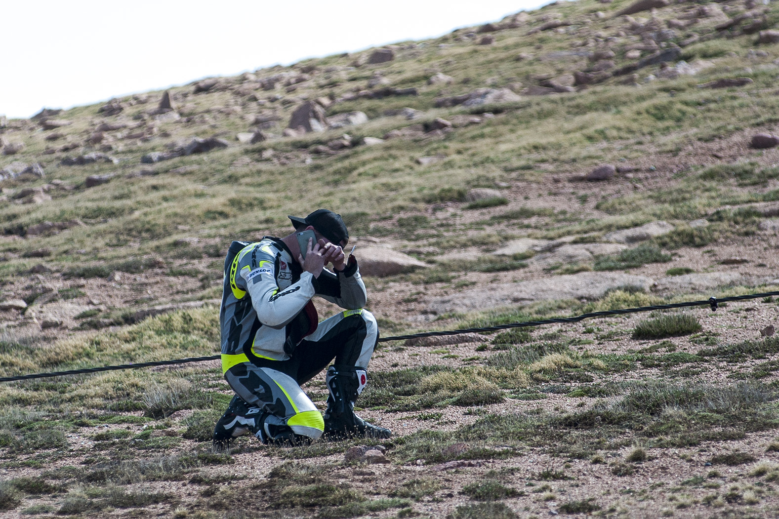 Motorcycle rider David Mobley kneels down to cry while talking on the phone to his father at Devils Playground near the summit of Pikes Peak on Thursday, June 25, 2015, in Colorado Springs, Colorado. Mobley learned only moments earlier that his good friend and fellow rider Carl Sorensen of Centennial, Colorado, slipped off the side of the Pikes Peak highway and died during his last practice run of the day.