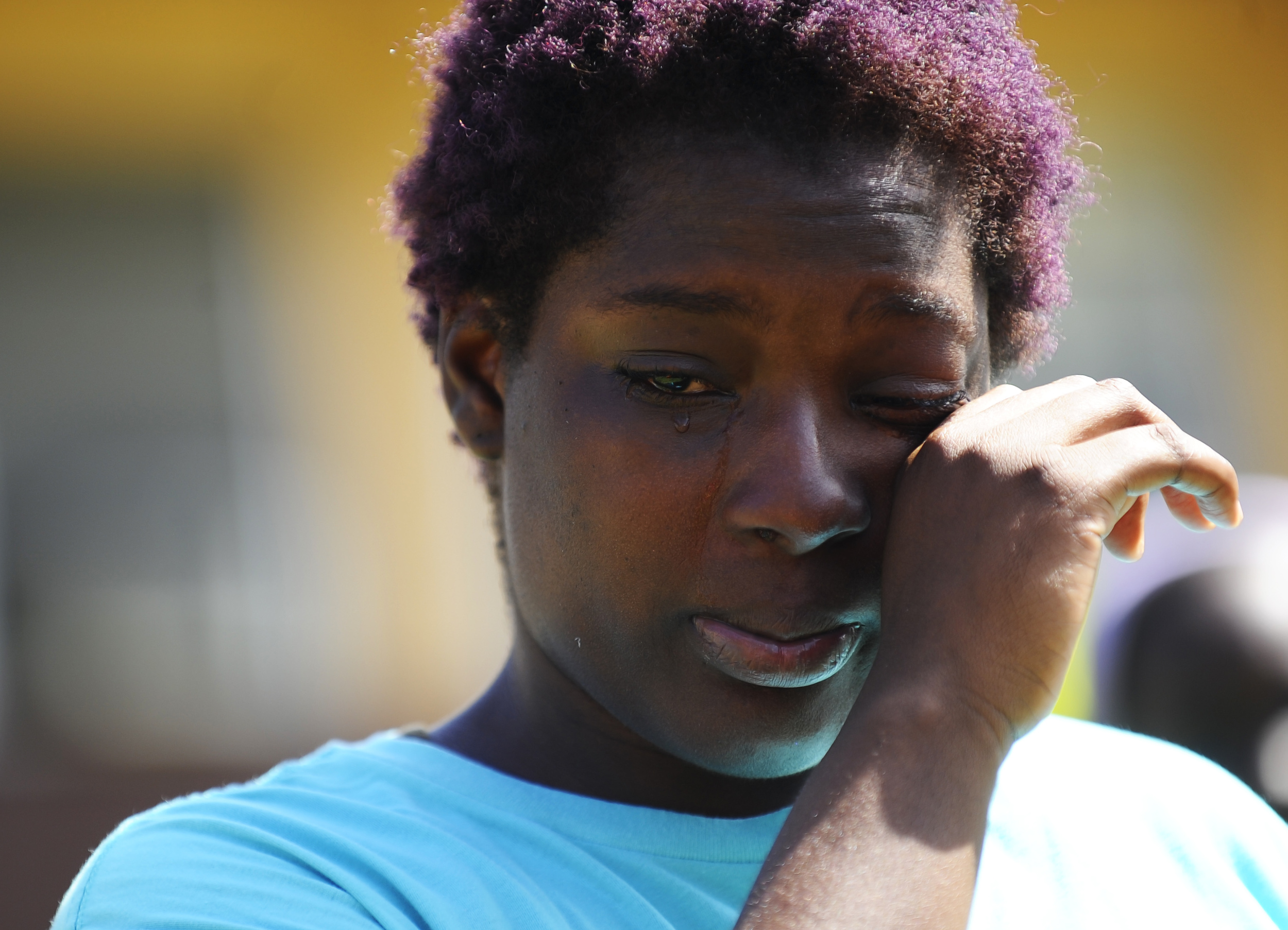 Liberty City community member Quanisha Williams wipes away tears as she speaks about her younger brother Dandre Jackson who was shot to death during a memorial ceremony dedicated to the children/youth and loved ones of those in the community who have lost their lives either through gun violence or natural causes on June 24, 2016.