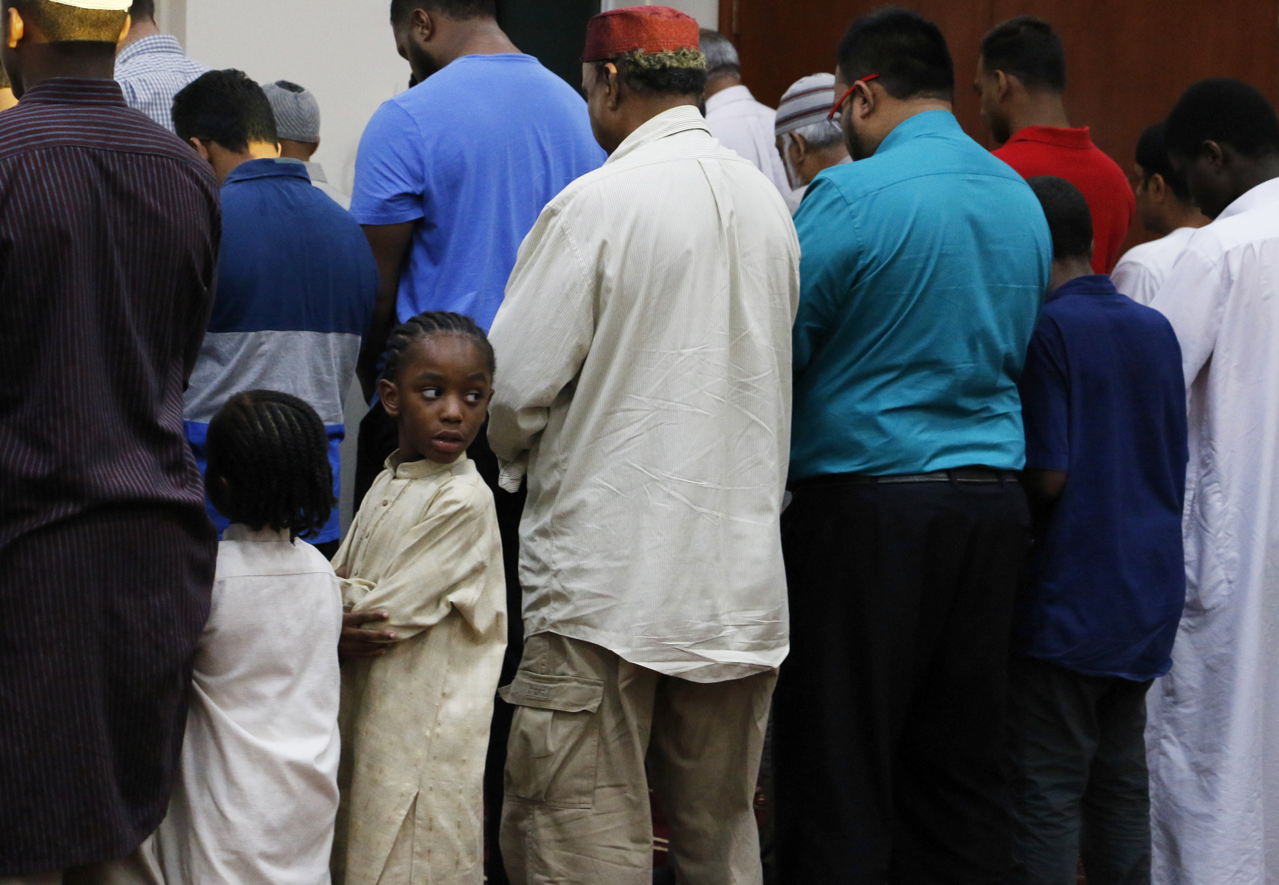 Diane Cooper, 5, stands with other Muslim men prior to prayer during the Ramadan Open House at Masjid Miami Gardens on June 9, 2016. The public was invited to a dinner as the fast of Ramadan is broken.