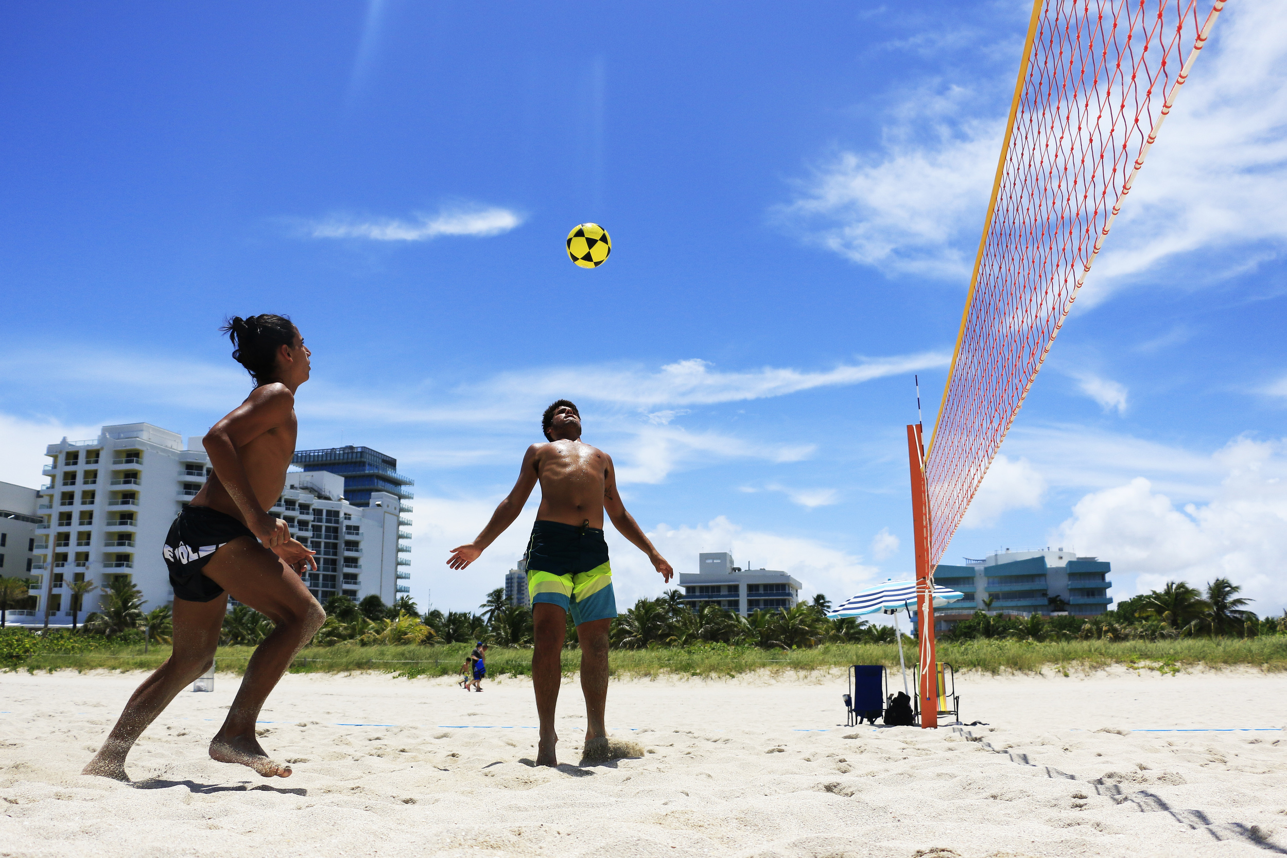 Diogo Nanni of Rio De Janeiro, Brazil, chests the ball while his teammate Gabriel Bonilla watches during a game of foot volley on South Beach during Fourth of July festivities.