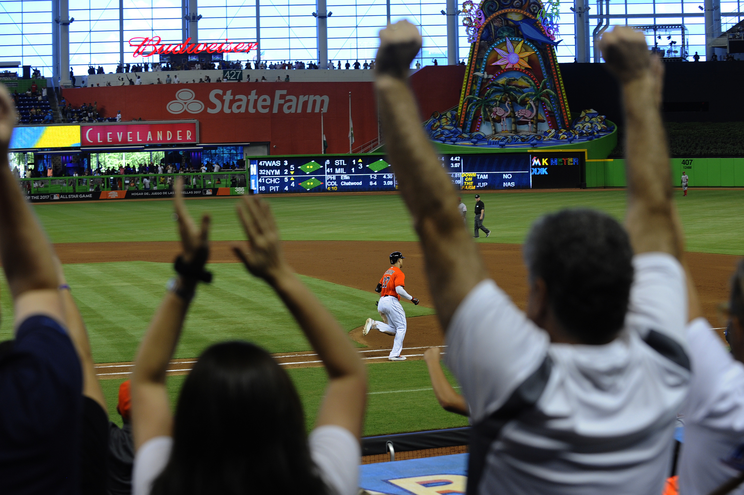 Fans celebrate as Miami Marlins right fielder Giancarlo Stanton (27) heads around the bases after hitting a home run during their game against the Cincinnati Reds at Marlins Stadium on July 10, 2016.