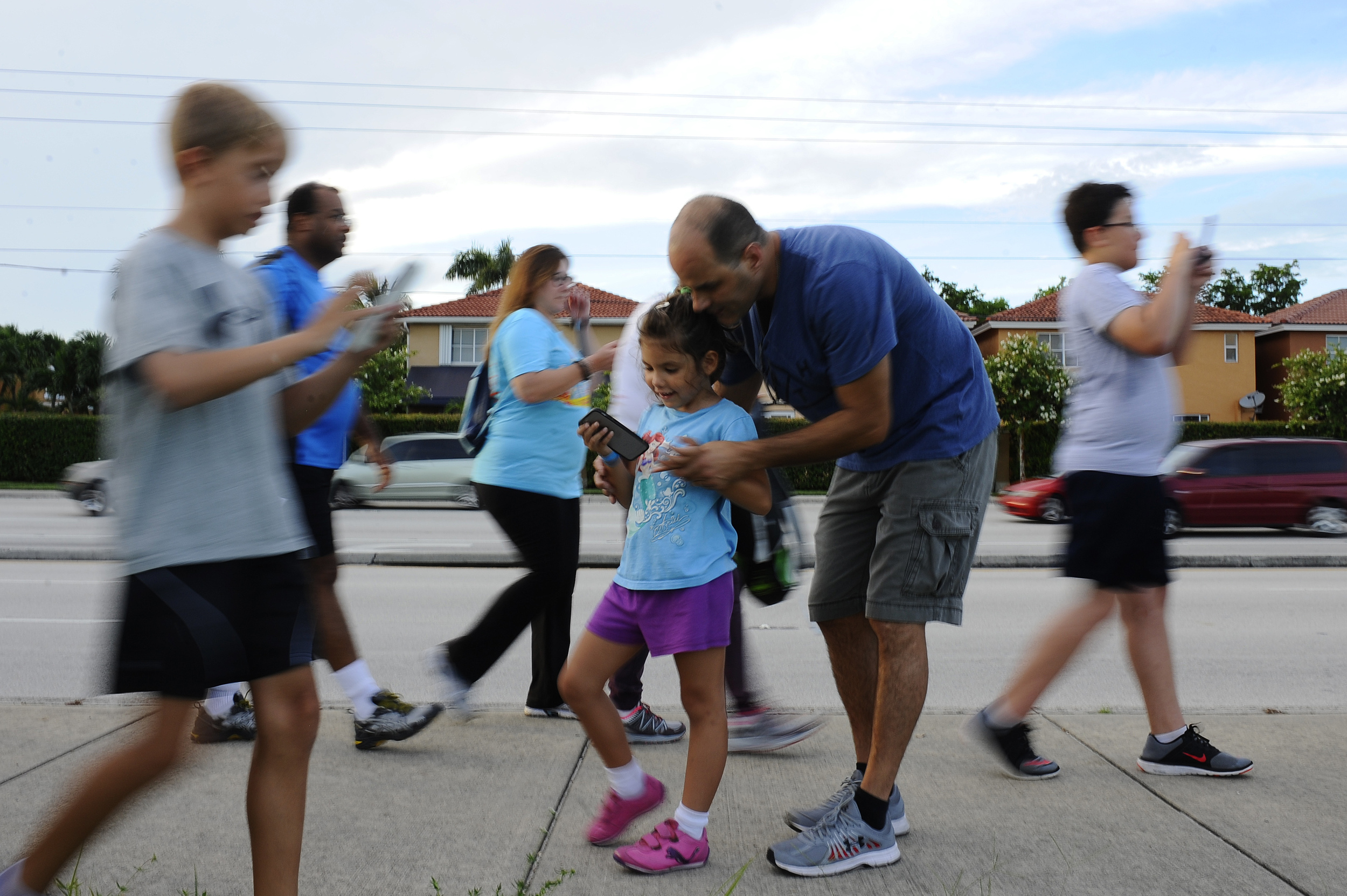 Andrea Olviera, 5, receives help from her father Alex Olviera with catching a Pokemon throughout the course during the weekly meeting of the West Kendall Baptist Hospital Run Club held at the West Kendall Baptist Hospital on July 21, 2016. The run club have introduced the popular app Pokemon Go into their runs in the hopes of getting more people engaged with others as well as getting in shape.