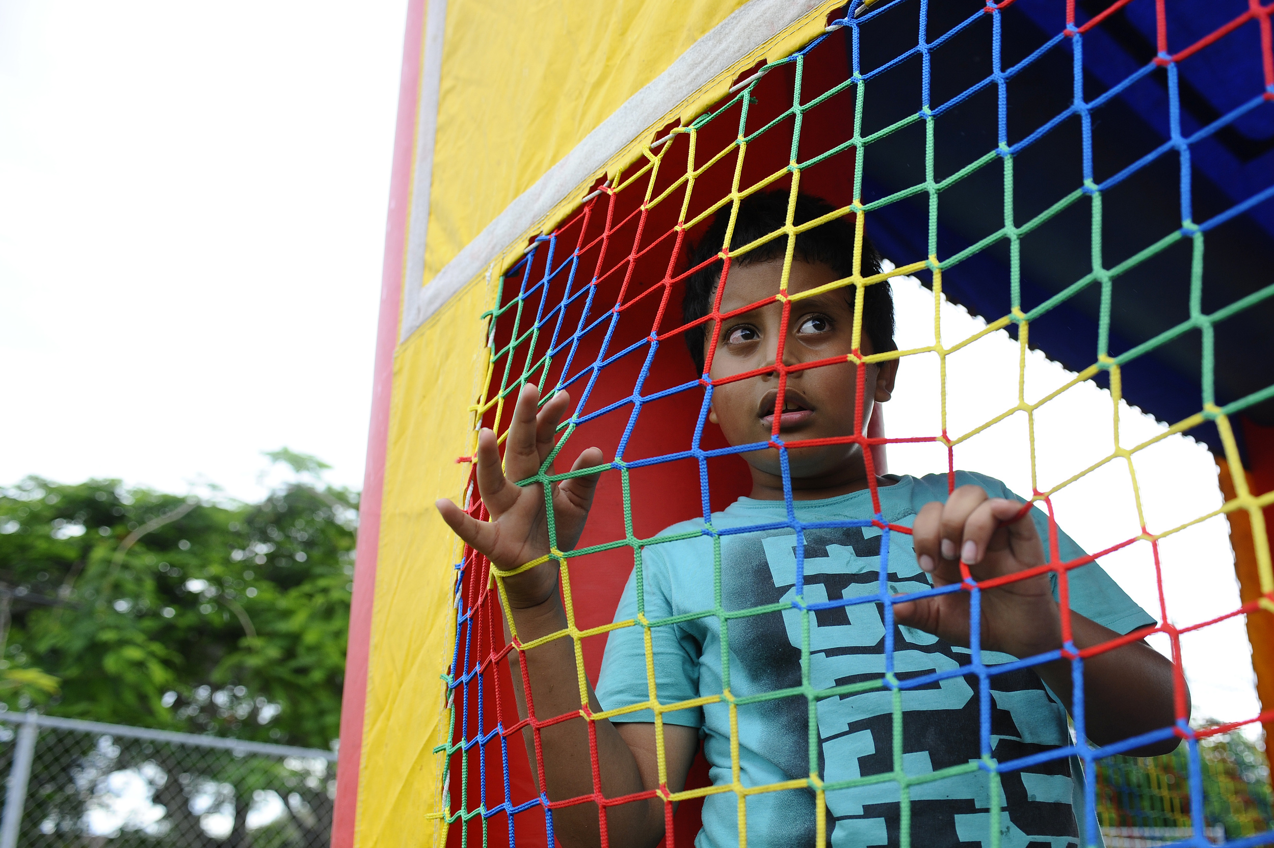 Ronald Salgado, 9, looks through the netting of a bounce house during a community event held in Homestead celebrating the 25th anniversary of the Centro De La Salle community center that has assisted and protected many young undocumented children and families.