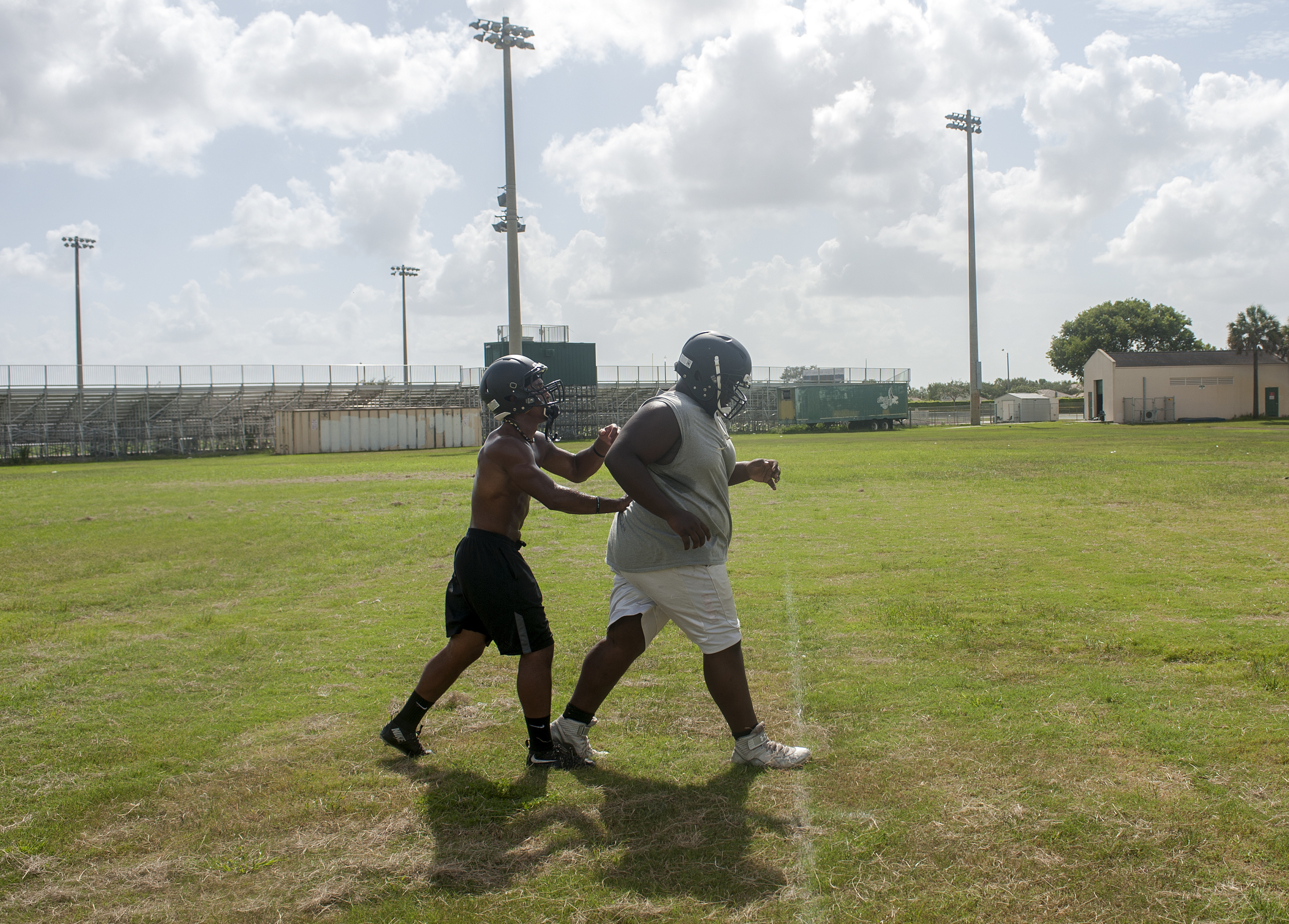 Flanagan high school senior wide receiver Clevan Thomas helps one of his teammates during conditioning drills on the first practice of the high school football season at Flanagan High School on Monday, Aug. 1, 2016. The reigning state champions look to repeat again despite the loss of key players from last year.