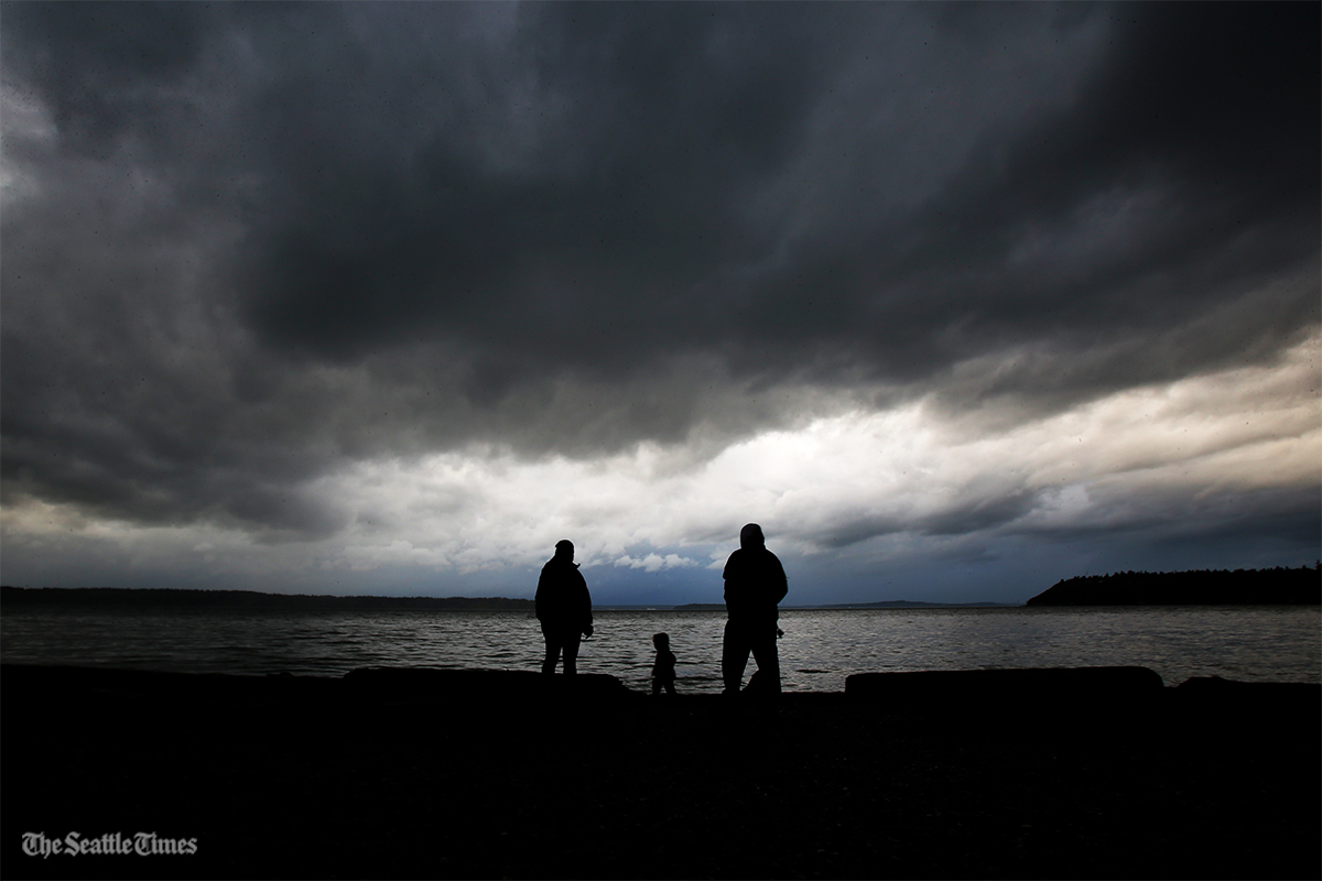 Melanie Fairbrook (left) and her husband David Washington (right) stand on the waters edge with their 2-year-old son Malcolm at Seahurst Park, in Seattle, Washington, on Saturday, October 15, 2016. Strong winds and heavy rain is expected to hit the northwest caused by remnants of a typhoon.