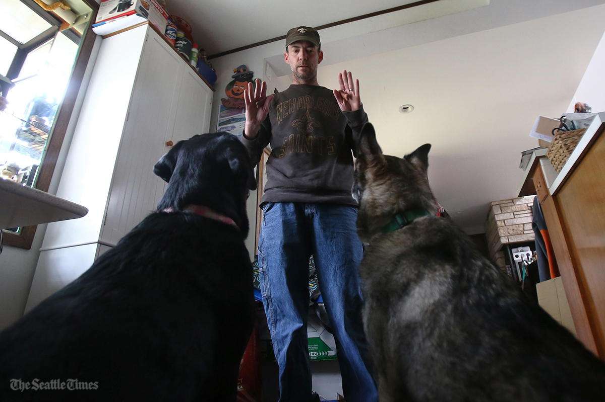 Trevor Rain-Water of Shoreline plays with his dogs Luke and Leah in his home on Monday, October 31, 2016. Rain-Water received a letter from the Regional Animal Services of King County who used direct mailing to target prospective pet owners with letters informing them of possible fines.