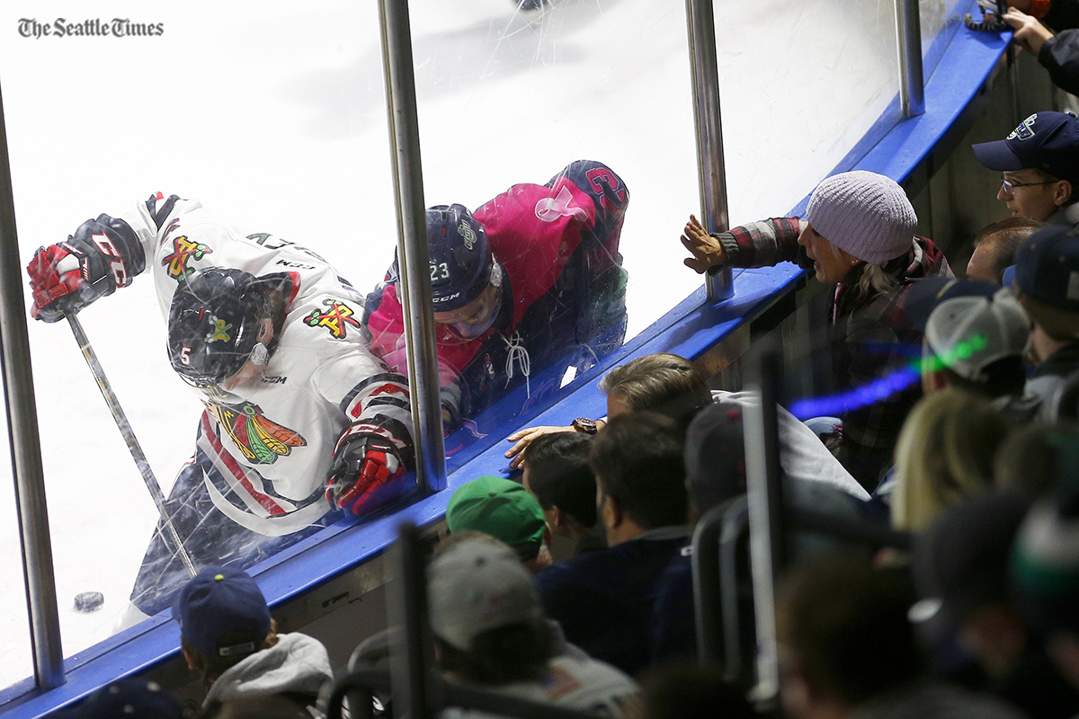 A woman bangs on the glass as Seattle Thunderbirds right wing Luke Ormsby (23) and Portland Winterhawks defenseman Matthew Quigley (5) fight for the puck during their game at the ShoWare Center on Friday, October 21, 2016.