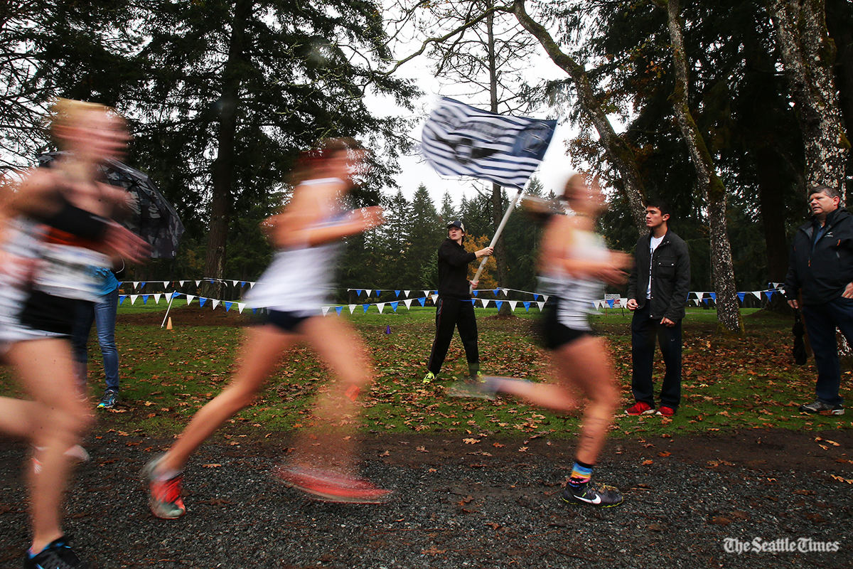 Zack Sundt of Olympia High School waves the school flag as runners pass in the class 4A meet during the Westside Classic District cross country meet at the American Lake Golf Course in Lakewood on Saturday, October 29, 2016.