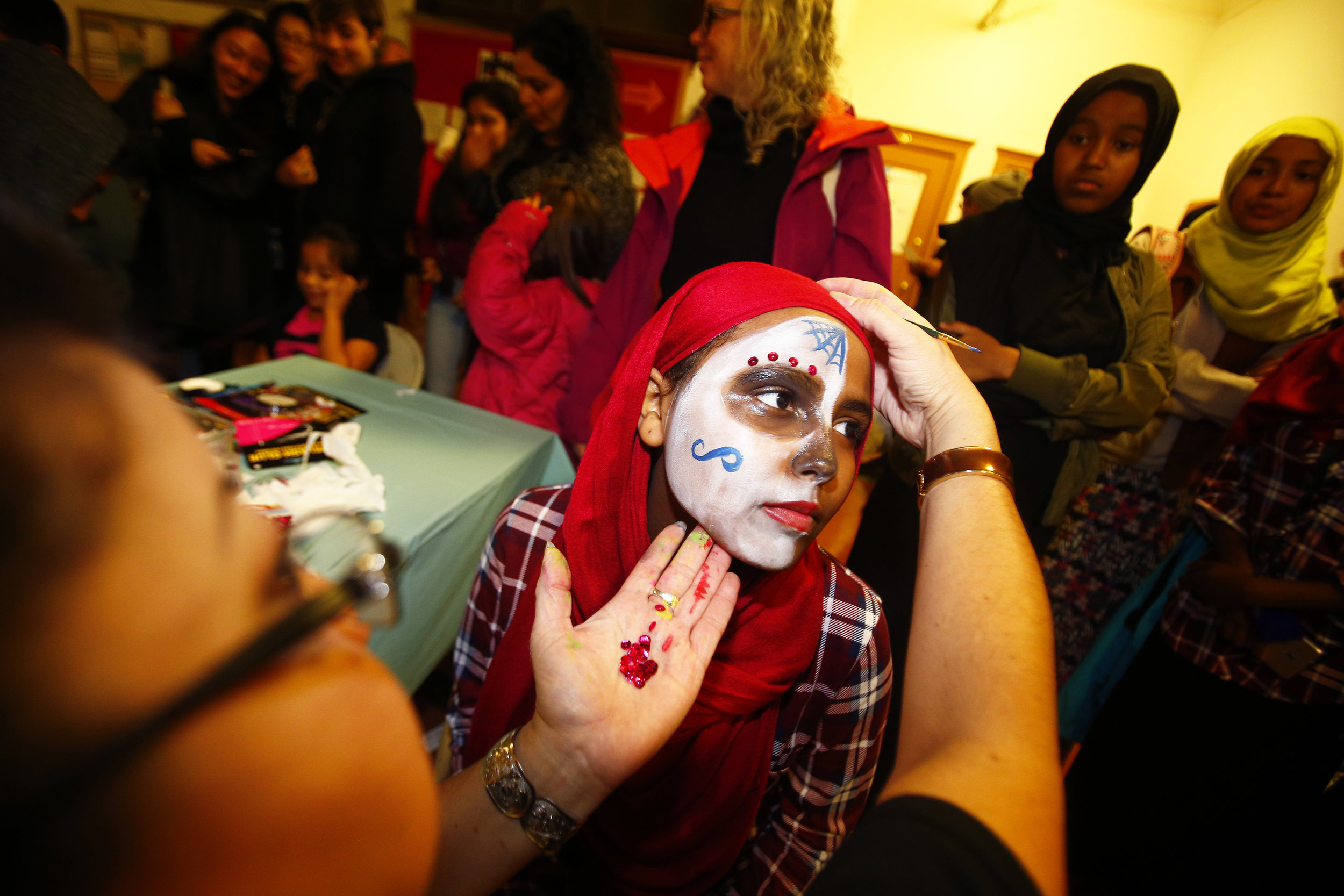 Anita Sharif of South Seattle, gets her face painted by first year artist Raquel Garcia during the 12th annual Dia De Los Muetos celebration held at the El Centro de la Raza in Beacon Hill on Tuesday, November 1, 2016. This year's Day of the Dead theme draws attention to systematic racial inequities and calls on people to exercise their right to vote in honor of those who have lost their lives.