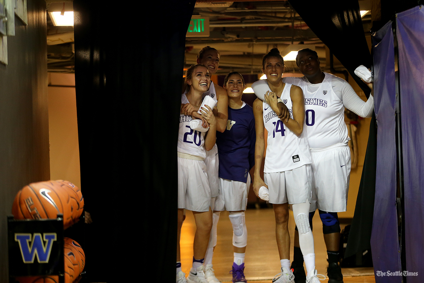 Members of the Washington Huskies women's basketball team look up at their Final Four banner being hung up prior to their game against Eastern Washington at the Hec Edmundson Pavilion on Friday, November 11, 2016.