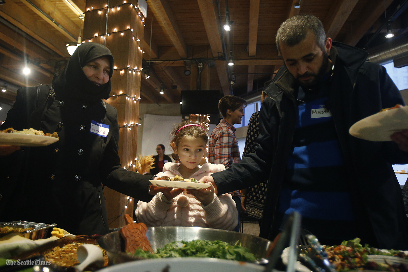 Mustafa Almustafa (right) helps his daughter Elaaf with her plate of food on Thursday, November 24, 2016, at the Impact Hub Seattle. Over 50 people from both sides of Puget Sound are donating food, supplies, and funds for the event, and the refugee families will be bringing some traditional dishes from their homeland to share with their new American friends.