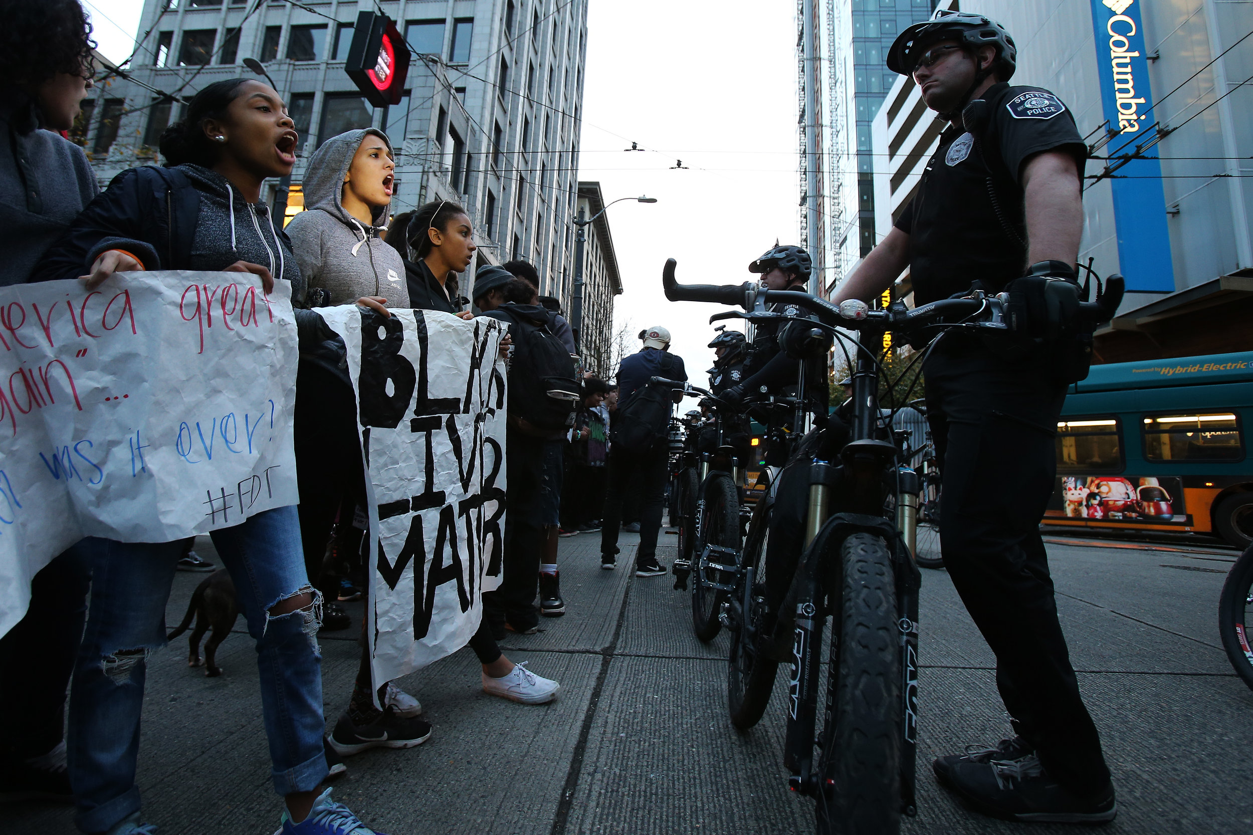 Protesters both students and adults yell at police in front of Westlake Park prior to making their way through downtown Seattle as police keep a watchful eye on Monday, November 14, 2016.