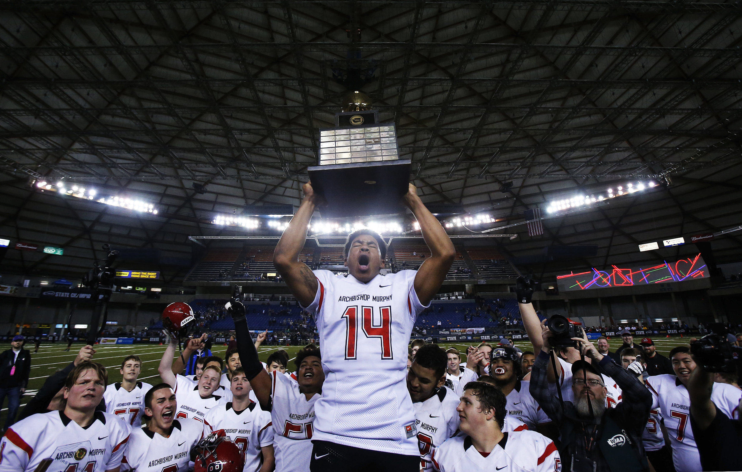 Archbishop Murphy Wildcats wide receiver Anfernee Gurley (14)celebrates by raising the 2A State Championship trophy after defeating the Liberty Patriots 56-14 on Saturday, December 3, 2016, inside the Tacoma Dome.
