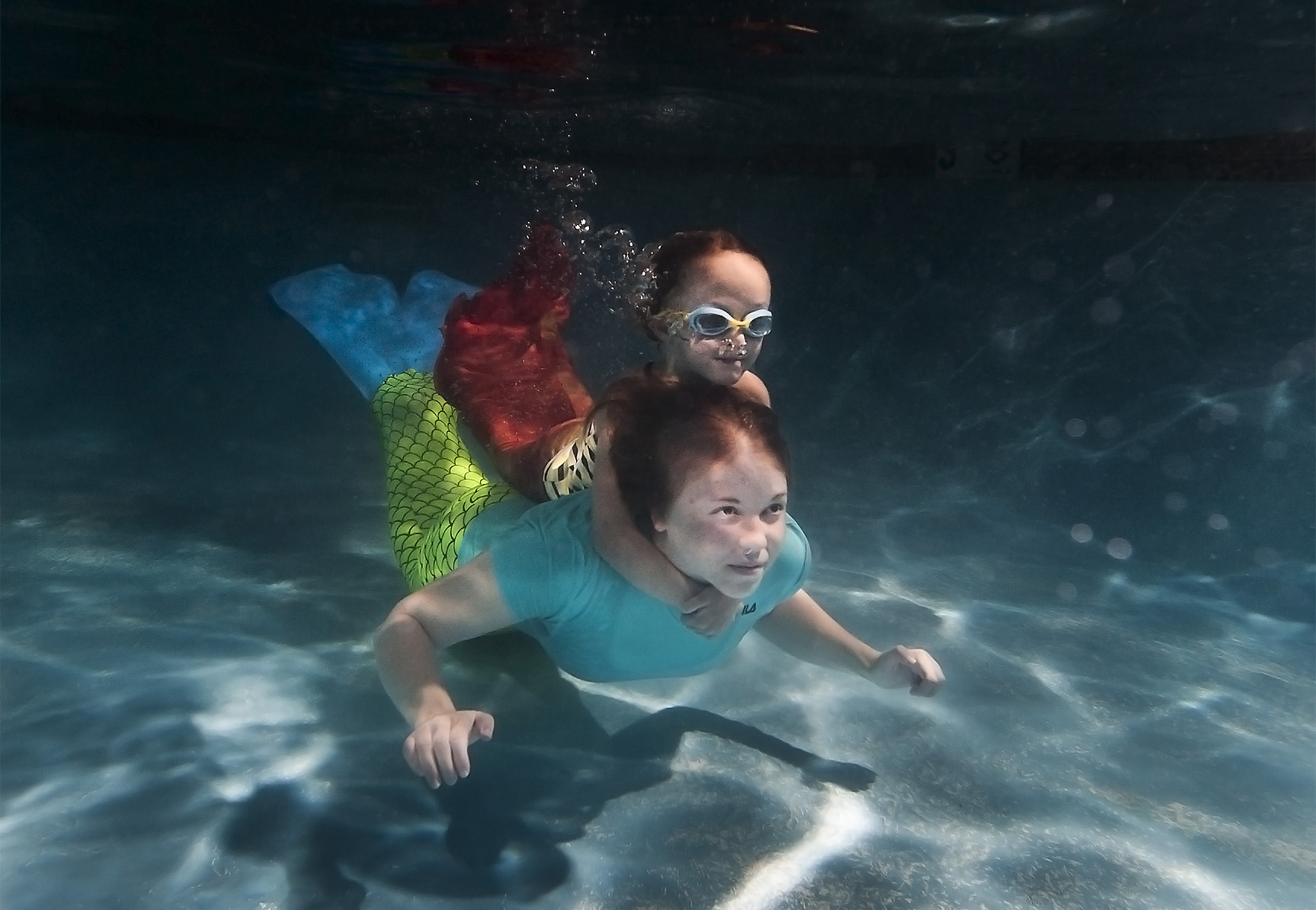 Charlotte Echols, 5, holds onto the neck of her swim instructor Julia Mortenson, 19, as they cross the pool underwater in mermaid swimsuits at the Mermaid Swim School located on Northpark Road in Colorado Springs on Thursday, July 23, 2015. The swim school offers mermaid classes to little kids and a monthly siren swim for adults who want to play in a pool wearing a mermaid tail.