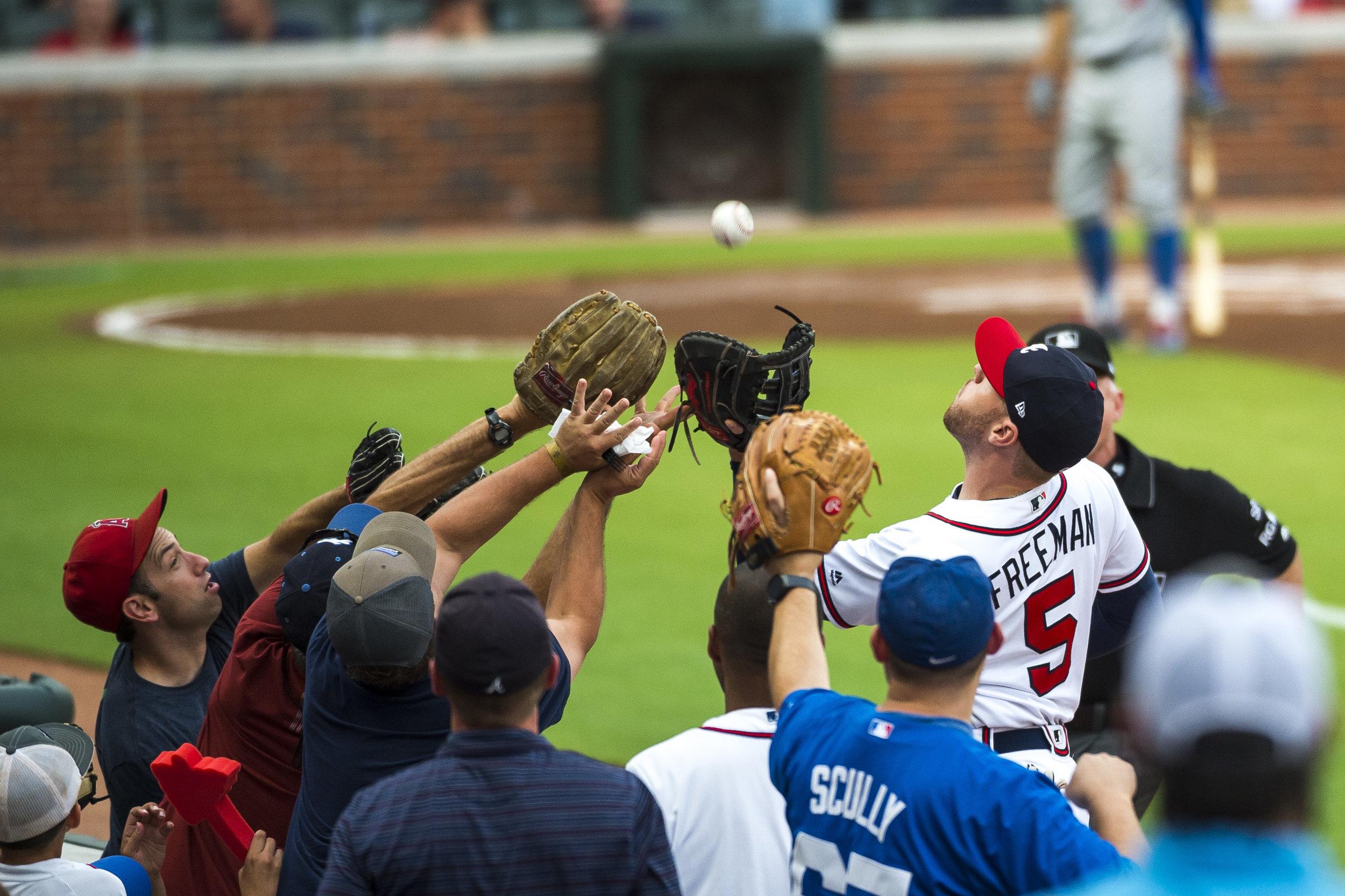 ATLANTA, GA - AUGUST 03: Freddie Freeman #5 of the Atlanta Braves fields a ball from fans against the Los Angeles Dodgers at SunTrust Park on August 3, 2017 in Atlanta, Georgia.