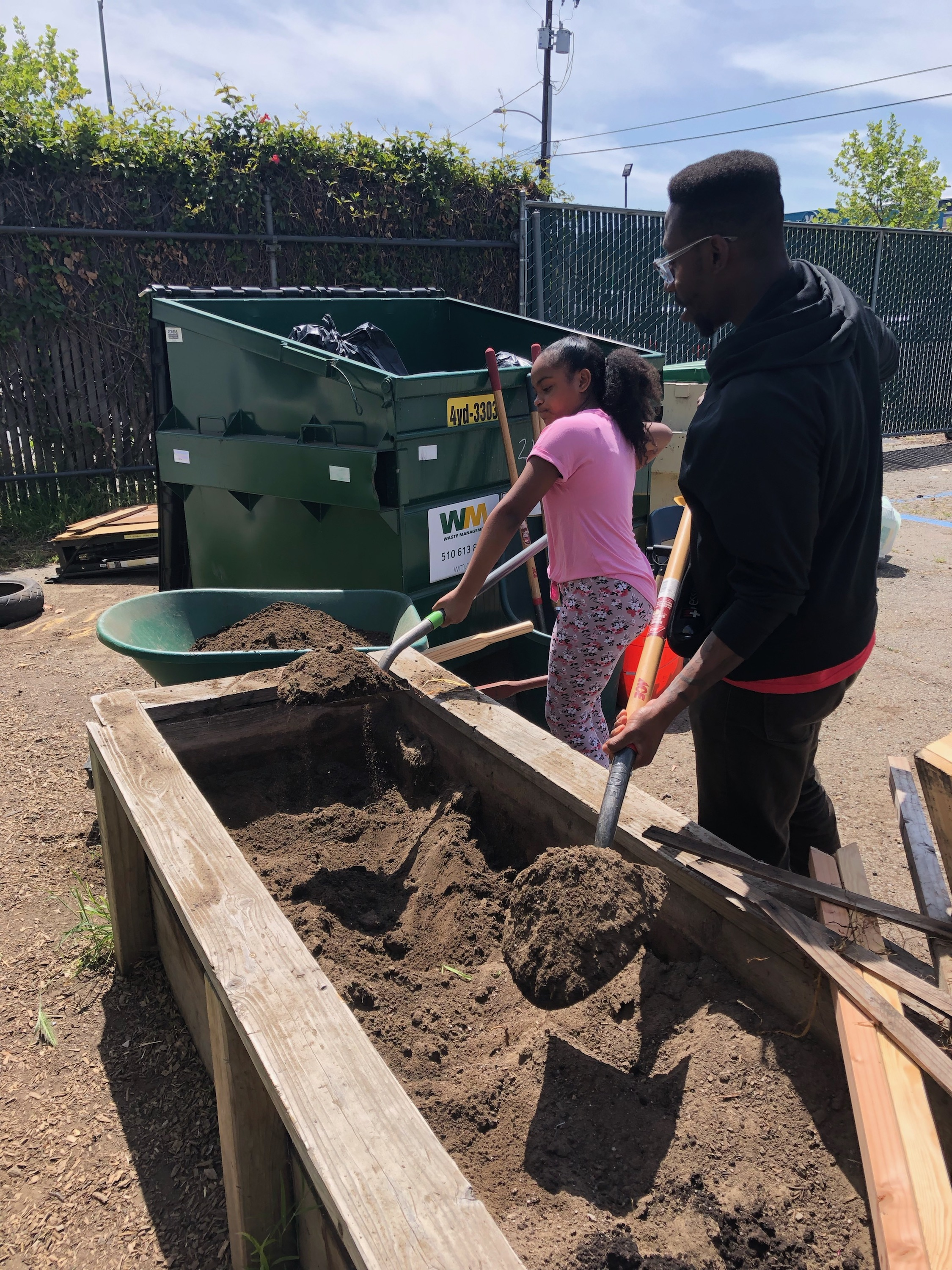 Staff member Malcolm, pictured to the right, assists a student shoveling new fertilizer into the planters-box.