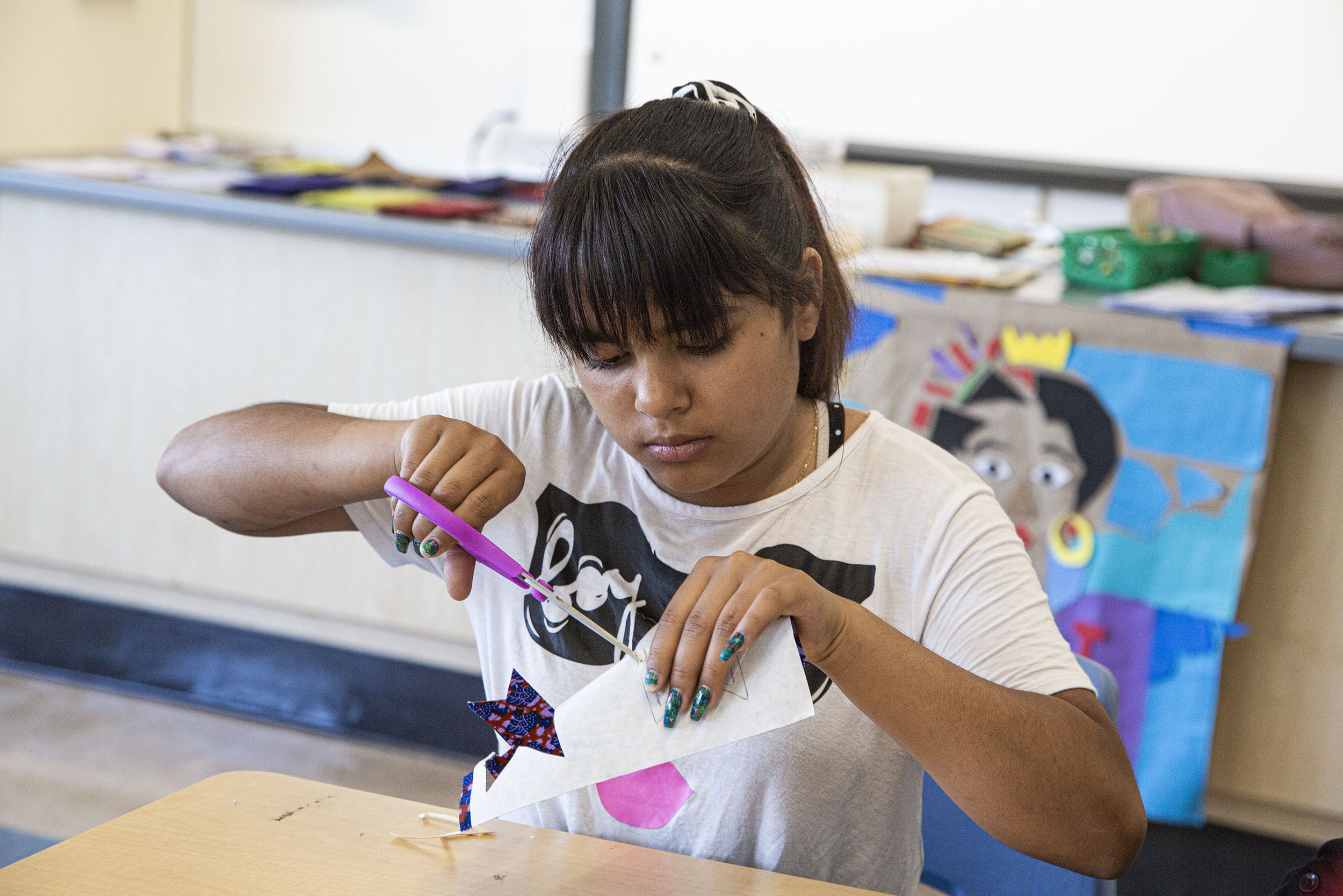 Student cuts out her first design (West Oakland Middle School)