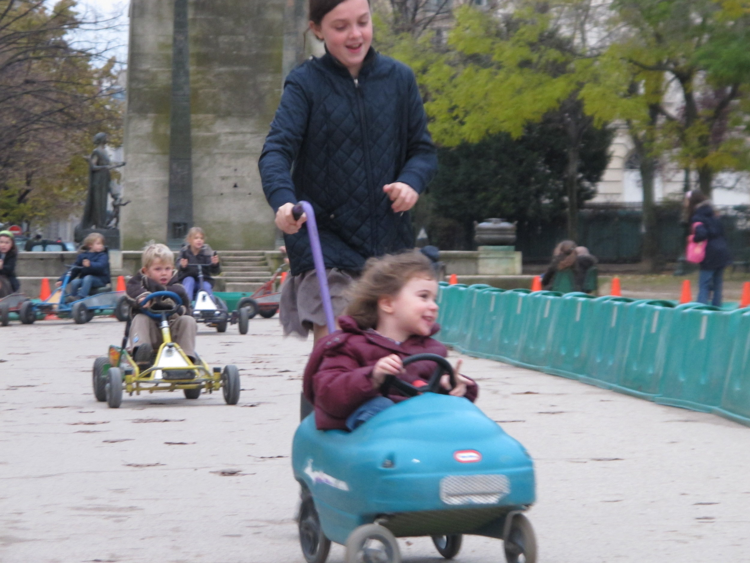 A young go-cart driver enjoying a little help from her  Maman  in the  Champ de Mars