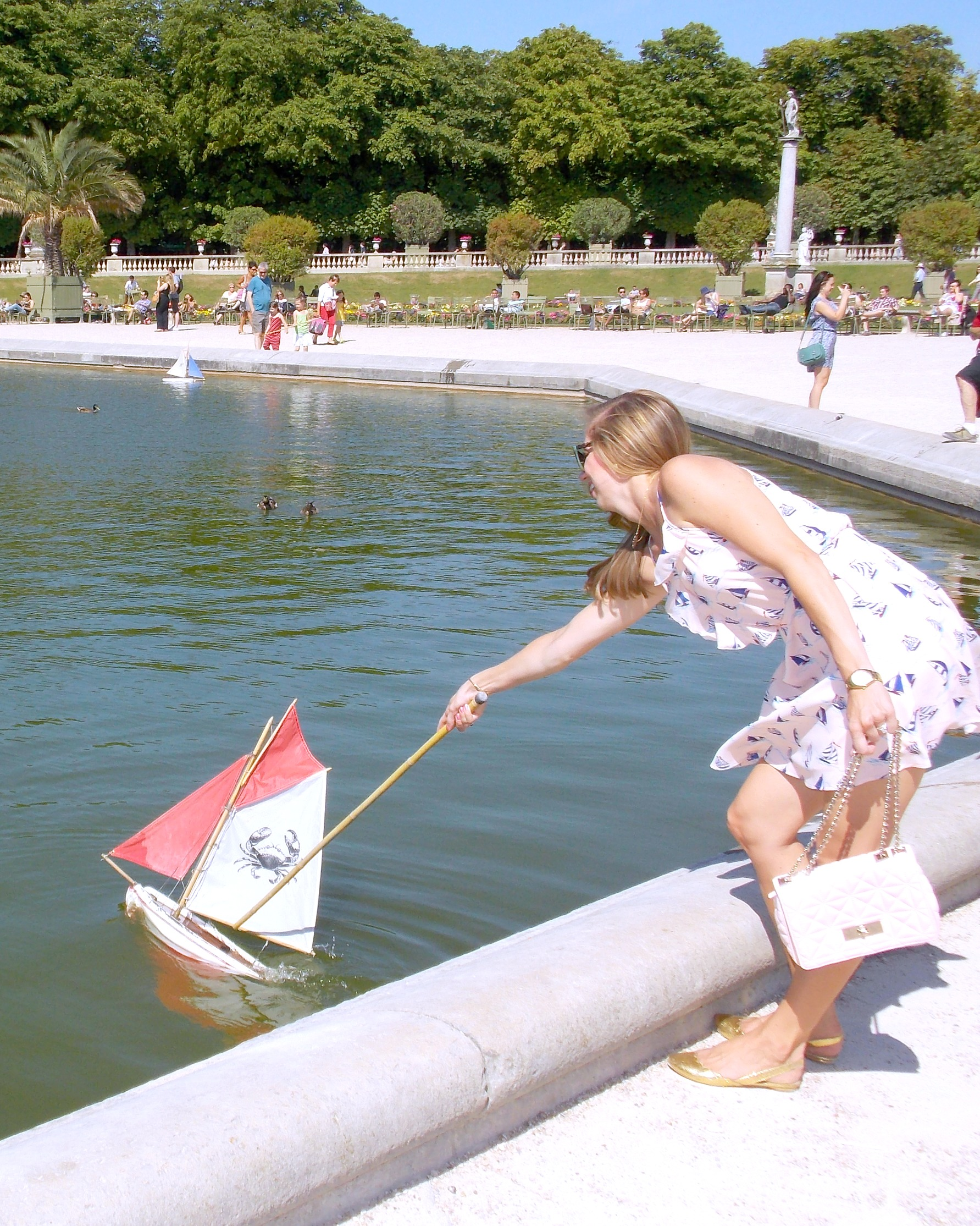 A woman getting her boat under sail in the  Jardins du Luxembourg.