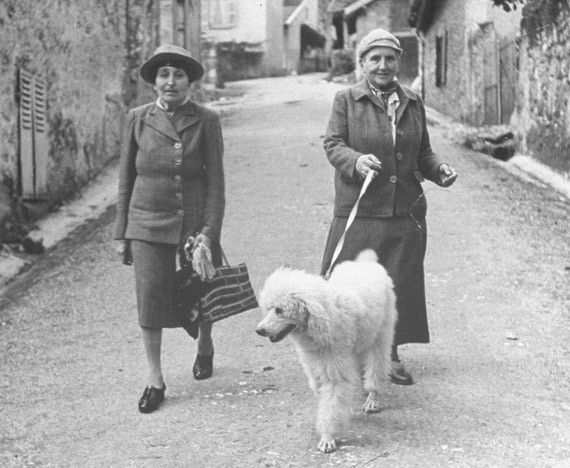 Alice B. Toklas and Gertrude Stein walking their poodle, Basket, a few years after Stein's novel  The Autobiography of Alice B. Toklas  made them both famous.