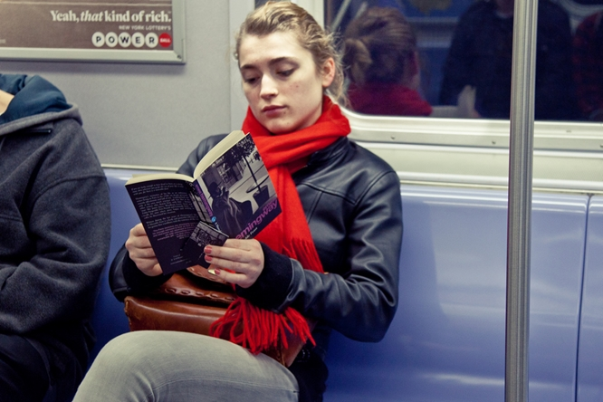 A young woman reading  A Moveable Feast  on the subway.