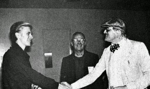 David Bowie (left) is introduced to Christopher Isherwood (right) by David Hockney (center) at the LA Forum, 1976. Photo Andrew Kent.