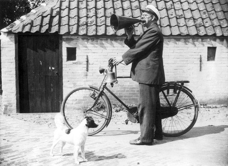 A town cryer in the town of Dorpsomroeper, probably The Netherlands. Notice the bell used to announce his arrival.