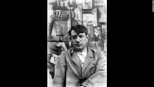 Picasso around 1911 in front of a cubist work.