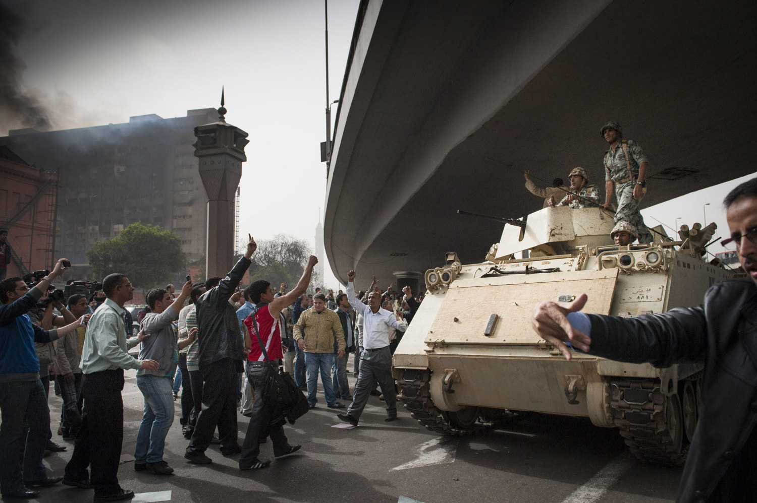 "Crowds cheer on the military as they enter the square as government building in the background still smolder from the ""Day of Rage"" on January 29, 2011."