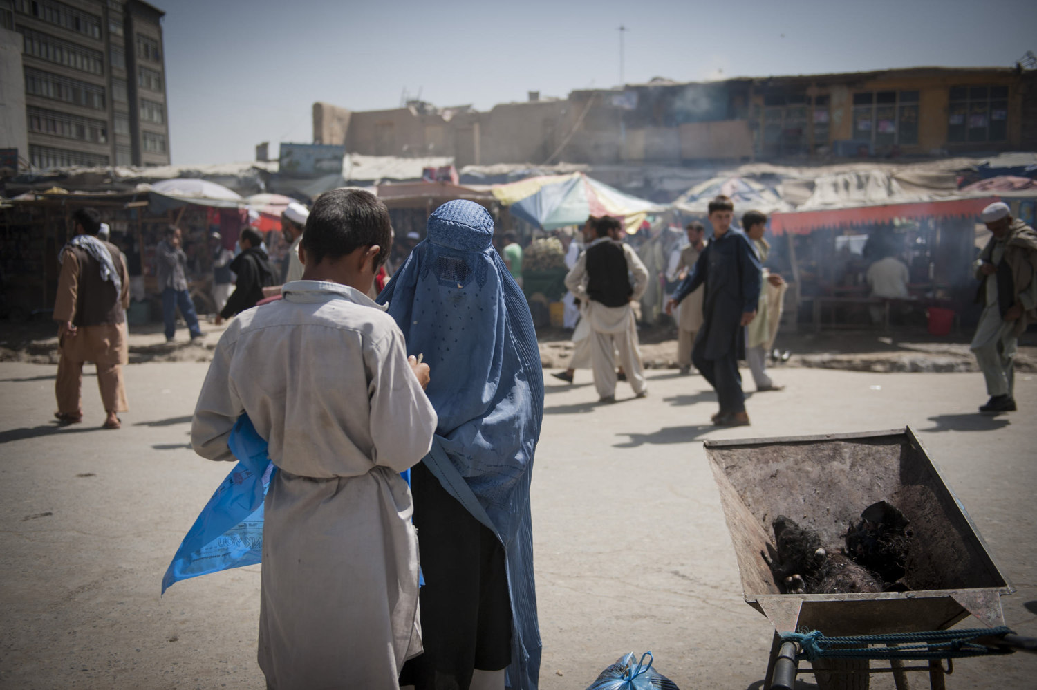 A burka clad woman purchases a calf head for a soup in a busy market near the Old City of Kabul, Afghanistan.