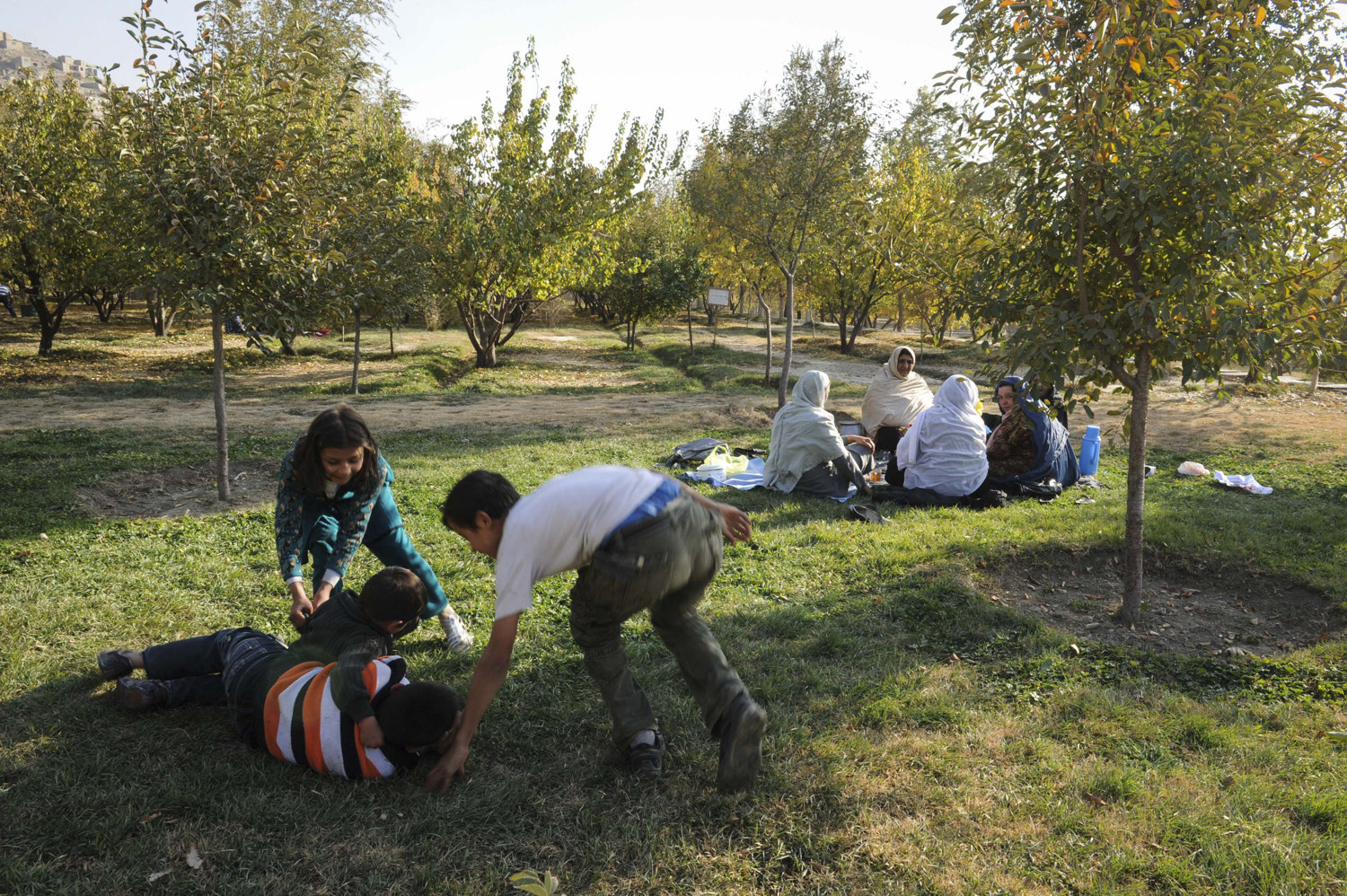 Children play on the grass at Bagh-e Babur historic park in Kabul Afghanistan while mothers watch nearby. The park is also the last resting-place of the first Mughal emperor Babur.