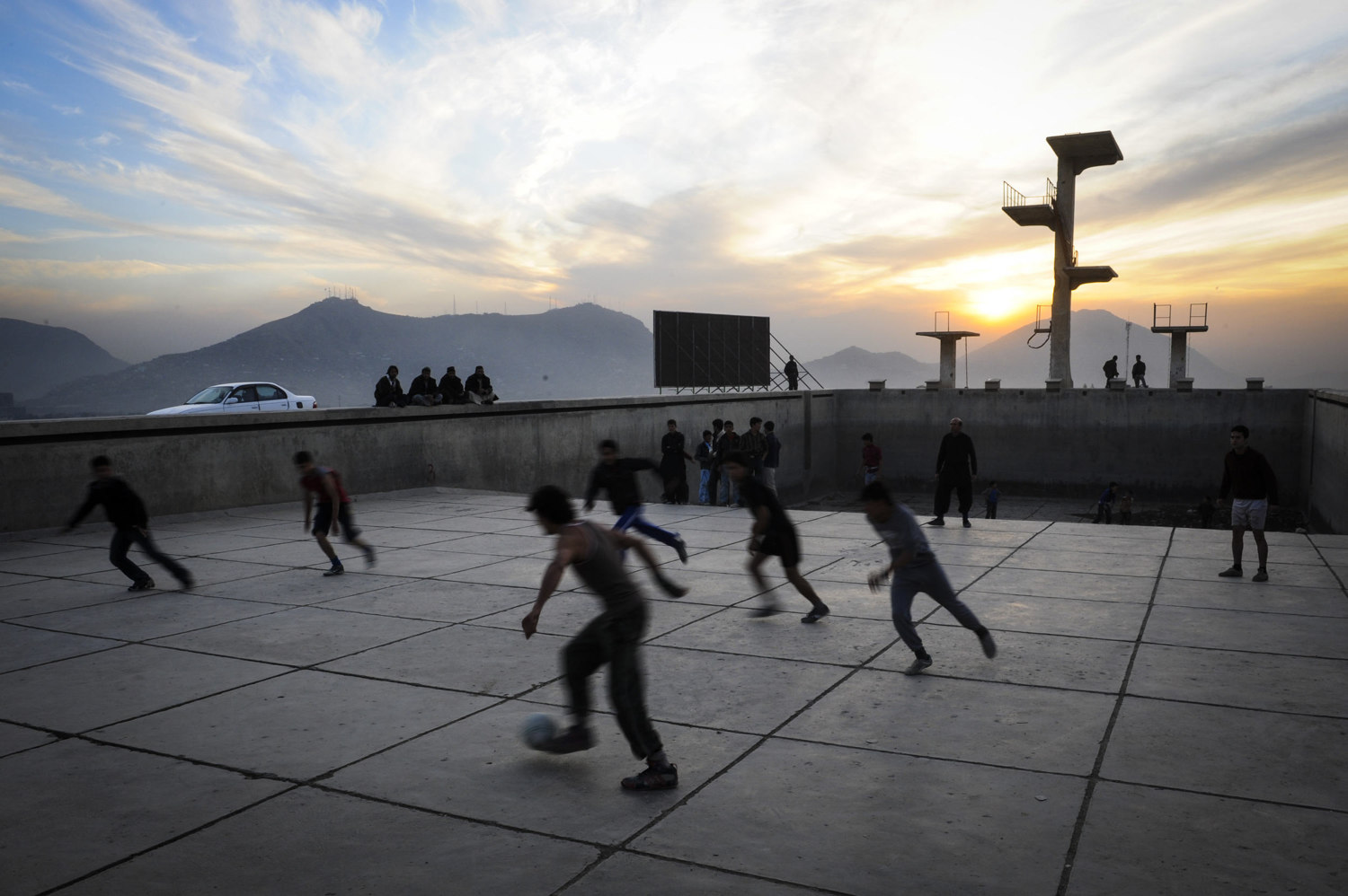 Boys and men play football in an empty pool at the top of Wazir Akbahan Hill. The pool was built by the soviets during their short occupation. Kabul, Afghanistan.
