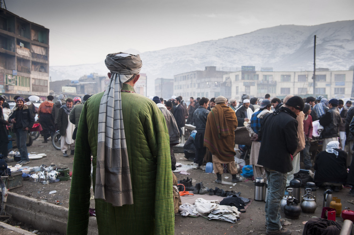 A man in traditional dress in a market in downtown Kabul. Most markets are unorganized and unregulated in Kabul as many salesmen cannot afford shops.