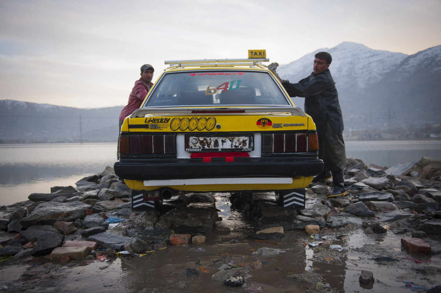 A car wash in the Kart-E Sakhi section of Kabul Afghanistan. It costs 150 AFS (roughly 3.00 USD) to wash a car in Kabul. The workers earn about 600 AFS or 12 dollars a day and work year round despite the sub-zero temperatures.