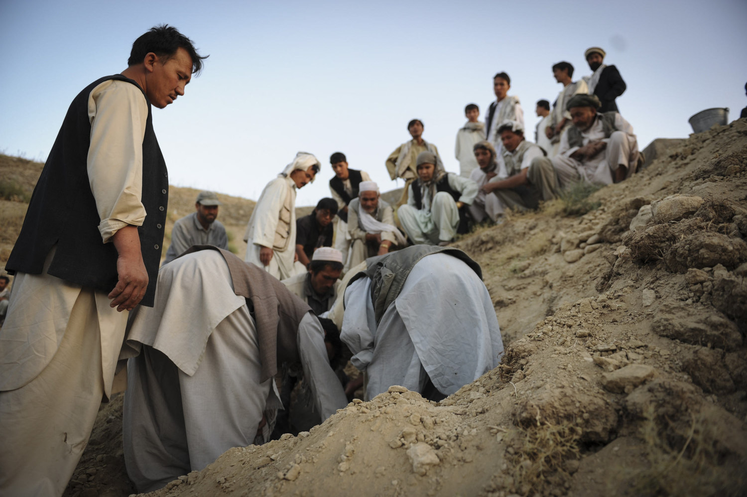 A Hazara funeral in Kabul, Afghanistan. In Afghanistan and most Muslim countries it is required to bury the dead before sunset. Only men attend the burial and women mourn at home.  The man on the left is the deceased son.