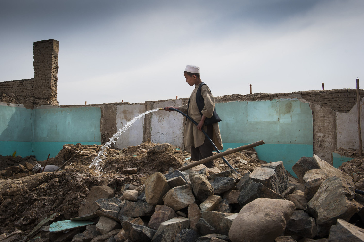 A workers son wets the rocks to cut down on dust and works on other small tasks around the construction site. Many male children are brought to work sites to assist their fathers. Day Laborer's chosen to work on rebuilding a house in  Kabul.