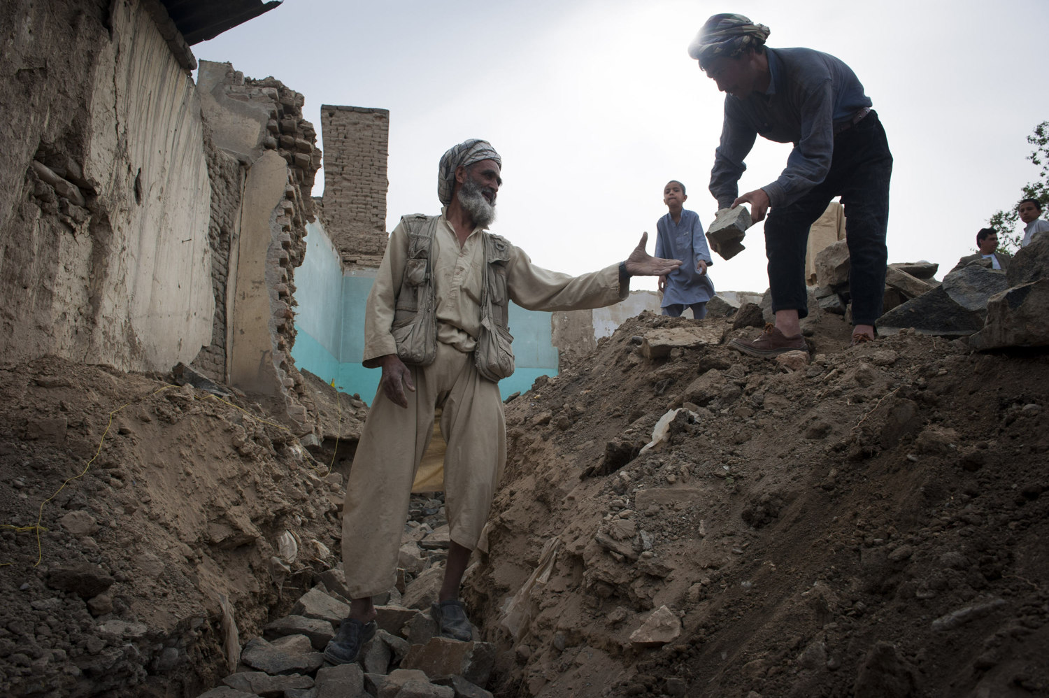 Sanangon, from Mazar Sharif lays rock in a trench that will be the foundation of the house in Kabul.The entire construction of the house will be done by unregulated labor.