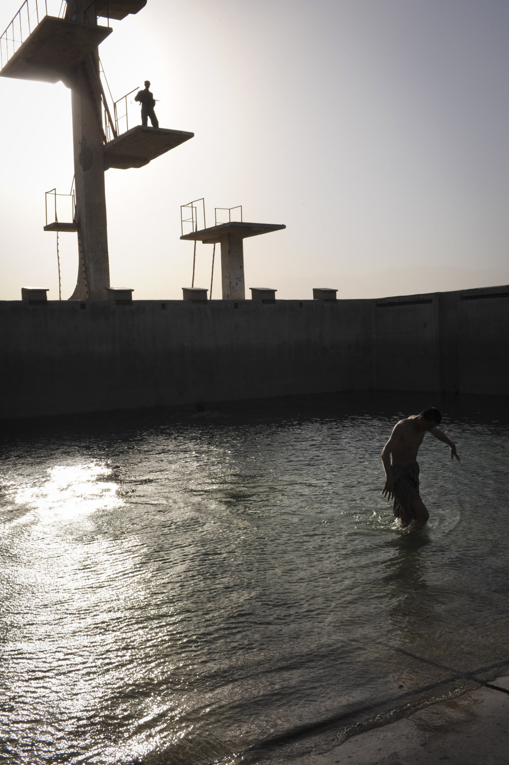 A man wades out of a pool while beign watched by an Afghan National Police man. Heightened security in Kabul the night before the election on Soviet Hill in Kabul Afghanistan, August 19th, 2009. The country later went on to elect incumbent president Hamid Karzai after months of debate over a tampered election.