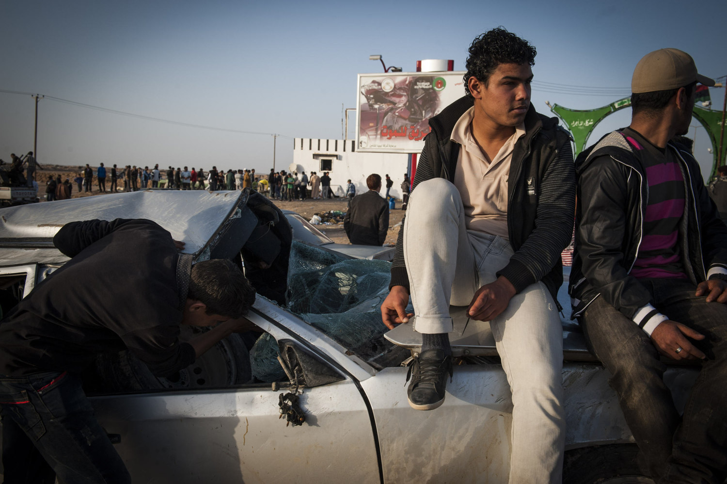 Boys sit on a broken car outside of the check point in Brega, Libya. Rebel troops are largely made out of Volunteers lack knowledge of military movement or weaponry.