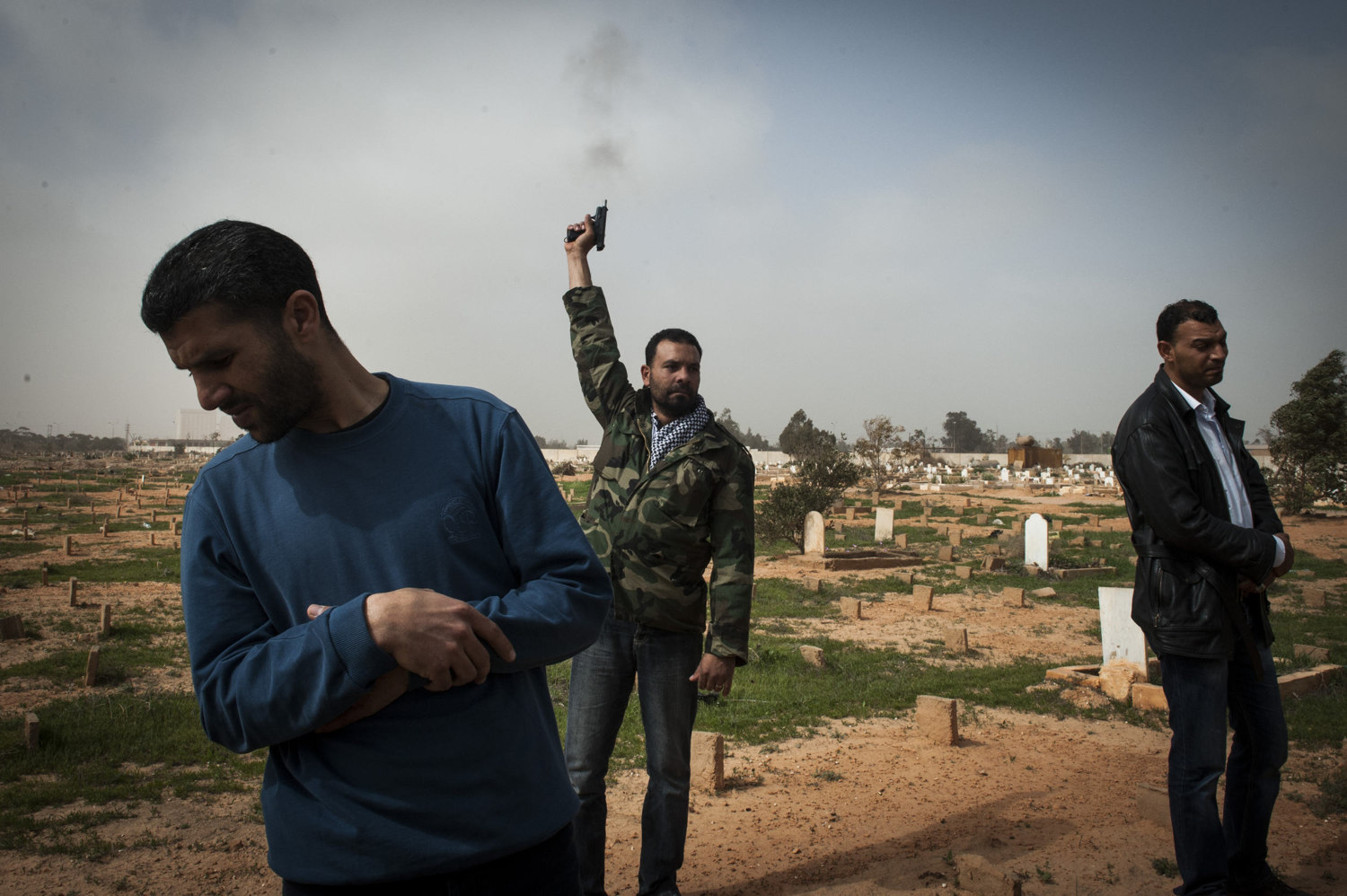 A man fires off a gun into the air to mourn. Men attend a mass burial at Benghazi Cemetery of seven men killed in an armory explosion the night before. It's not clear whether the armory exploded due to airstrikes or error by the soldiers.