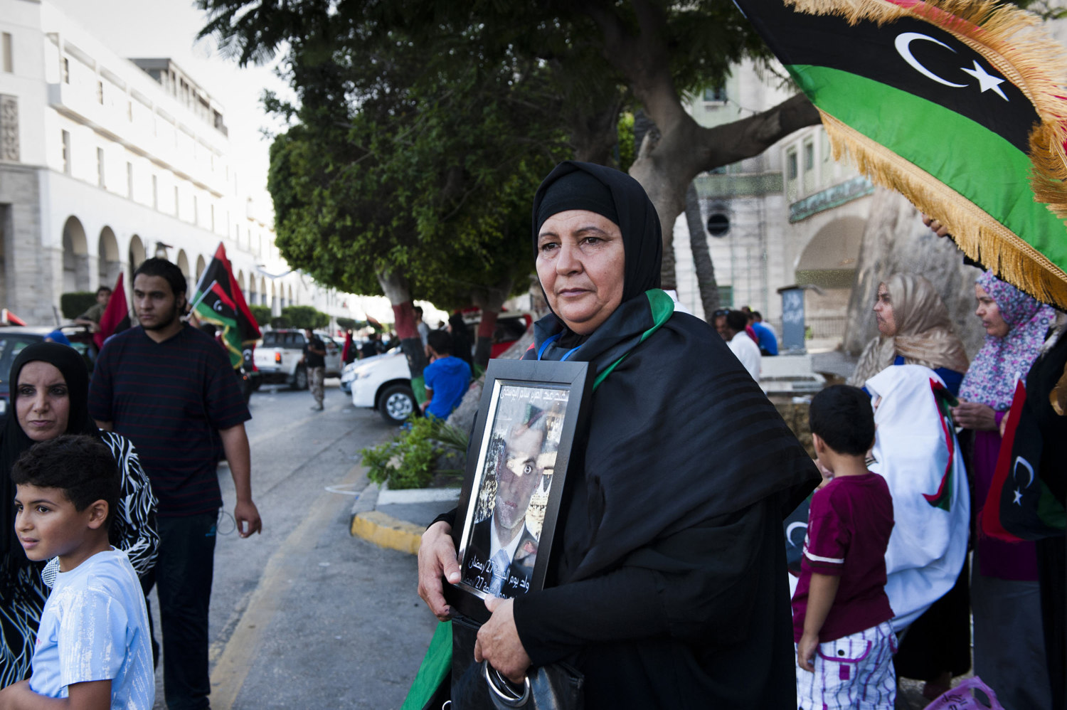 A woman holds a photo of her martyred son in downtown Tripoli as others celebrate the vote. Libyans celebrate after voting.After 42 years of Muammar Gaddafi's reign, Libyans are participating in the first democratic election since 1969.