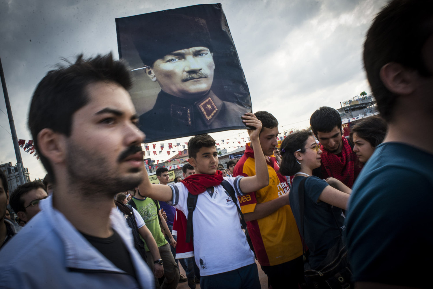A boy holds up a portrait of former leader Mustafa Kemal Ataturk in Taksim Square,  where yesterdays clashes occurred, June 2, 2013.