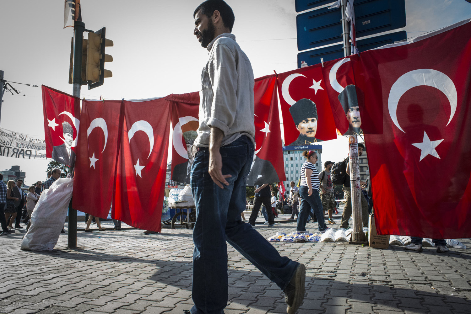 A man walks buy flags picturing the face of Ataturk, the founder of Modern Day Turkey on June 6, 2013.