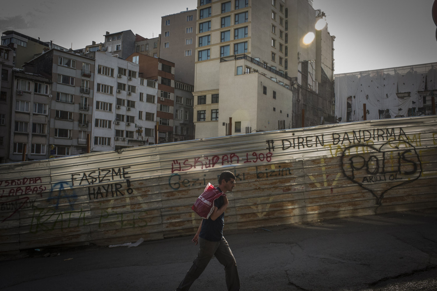 A man walks up a street adjacent to Taksim square in front of anti-government graffiti, where protesters have camped out for weeks. June 6, 2013.