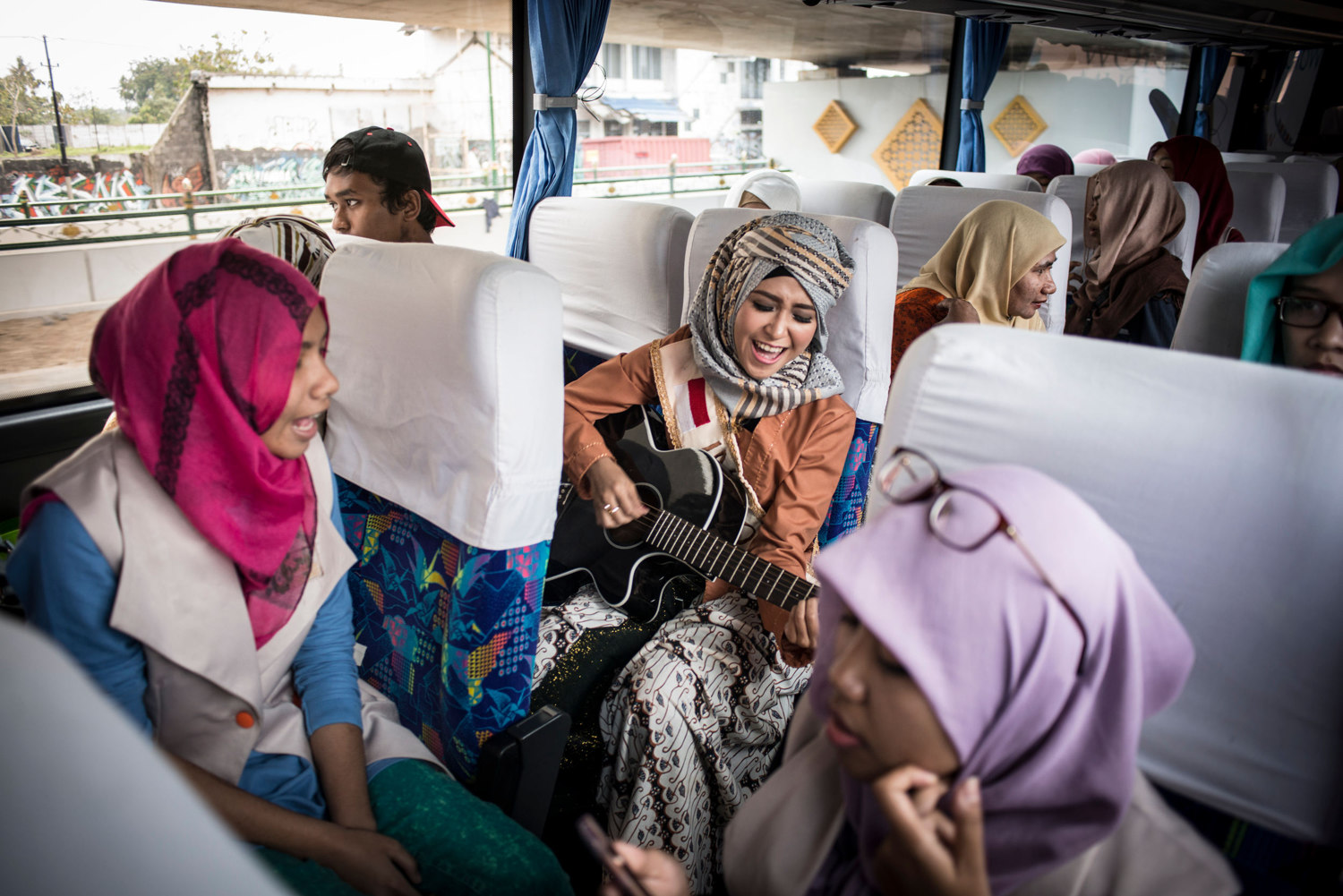 Indonesian finalist Elis Sholihah leads a sing-along on the bus between events.